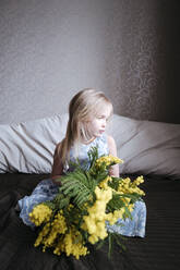Portrait of blond little girl sitting on bed with bunch of mimosa - EYAF00908