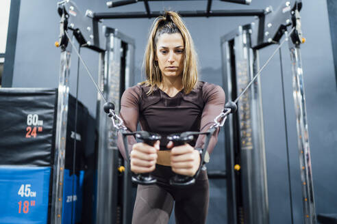 Woman exercising at cable machine in gym - OCMF01006