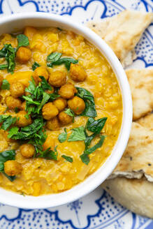 Vegan lentil curry with red lentils, sweet potatoes, spinach, roasted turmeric, chickpeas, with lime juice and coriander and naan bread - LVF08578