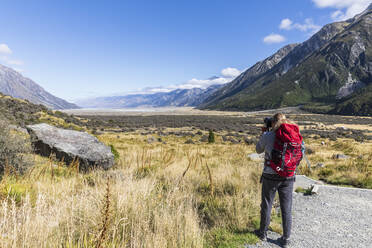 New Zealand, Oceania,South Island, Canterbury, Ben Ohau, Southern Alps (New Zealand Alps), Mount Cook National Park, Rear view of tourist photographing Tasman Valley - FOF11620