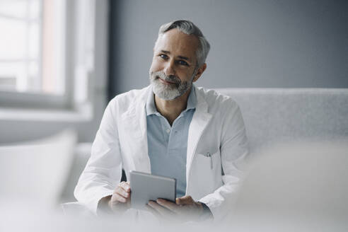 Portrait of smiling doctor with digital tablet - KNSF07356