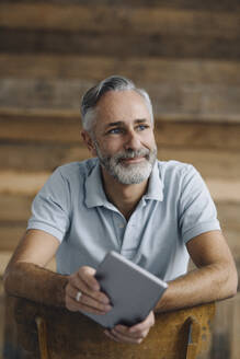 Portrait of smiling mature man with digital tablet leaning on back rest looking at distance - KNSF07362