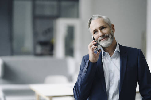 Portrait of smiling mature businessman on the phone - KNSF07368
