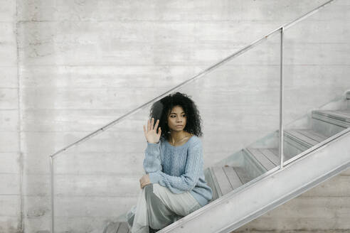 Beautiful young woman sitting on stairs behind a glass pane - TCEF00099