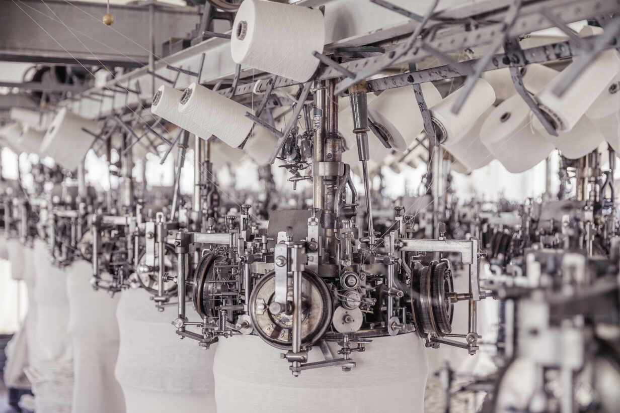 White cotton reels on a machine in a factory - SDAHF00048 - Floco Images/Westend61