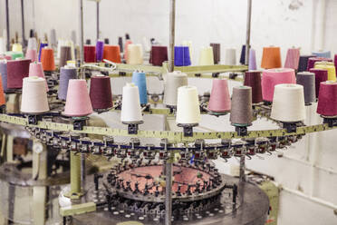 Multicolored cotton reels on a machine in a factory - SDAHF00054