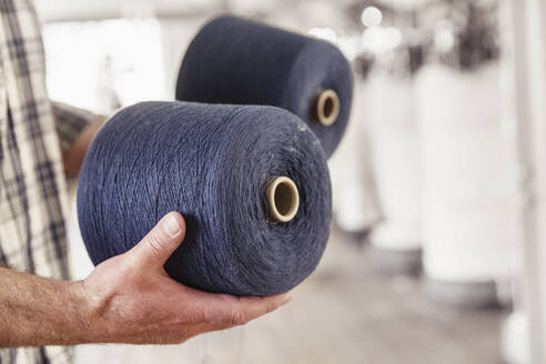Close-up of man holding cotton reels in a textile factory - SDAHF00066