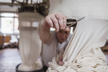 Close-up of man working in a textile factory cutting cloth - SDAHF00069
