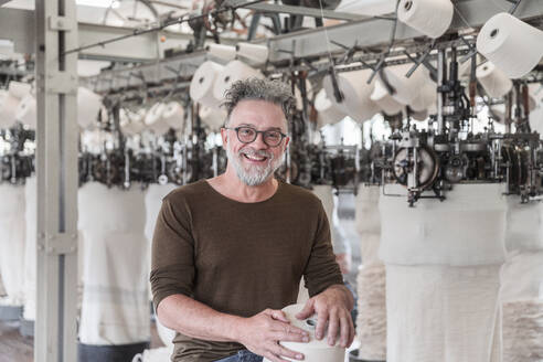 Portrait of a happy mature man in a textile factory - SDAHF00072