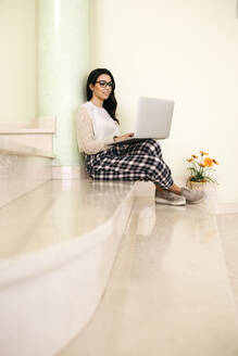 Young woman sitting on stairs using laptop - JRFF04067