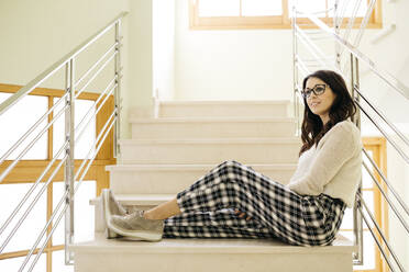 Young woman sitting relaxed on stairs - JRFF04076