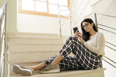 Young woman sitting on stairs using cell phone - JRFF04079