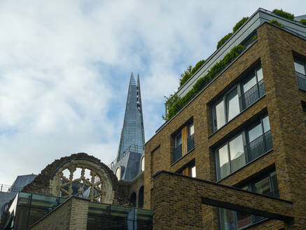 England, London, Low angle view of apartment building with Shard skyscraper in background - LOMF00983