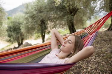 Girl resting in hammock in an olive grove - BFRF02191
