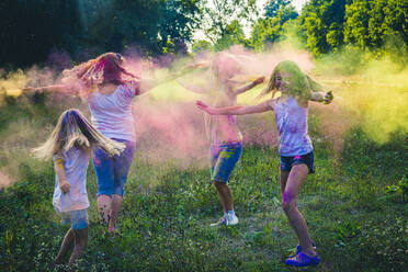 Group of two women and two girls celebrating Festival of Colours on a meadow - SARF04454