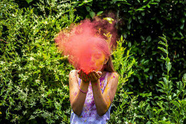 Girl blowing red powder paint in nature - SARF04457