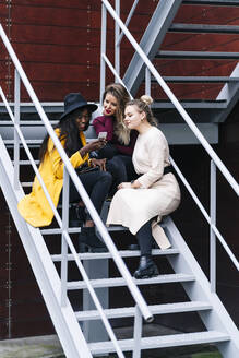 Girlfriends sitting on stairs outdoors looking at mobile phone - DGOF00174