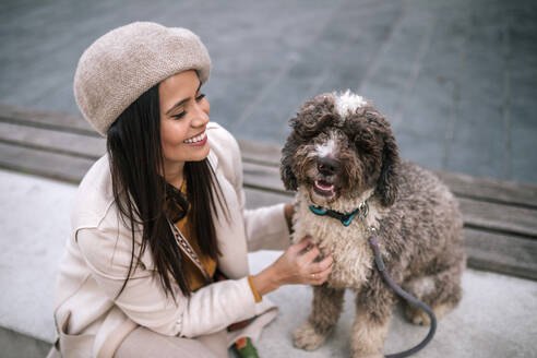 Happy young woman stroking her dog in the city - GRCF00138