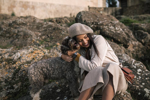 Happy young woman cuddling her dog in the city - GRCF00144