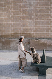Young woman with her dog in the city giving paw - GRCF00150