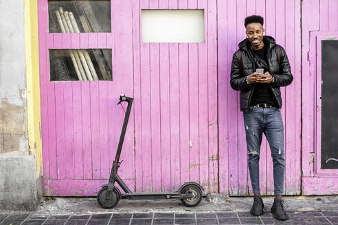 Portrait of smiling man with smartphone and e-scooter outdoors - RCPF00213
