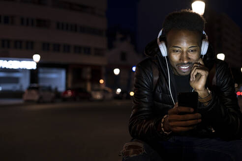 Man in the city at night with smartphone and headphones - RCPF00228