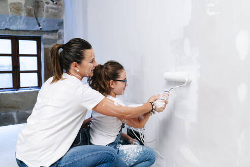 Mother and daughter painting a wall of her new house together - DGOF00220