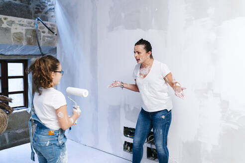 Mother arguing with her daughter while painting a wall of her new house - DGOF00229