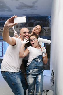 Happy family taking a selfie while painting the walls of her new house - DGOF00241