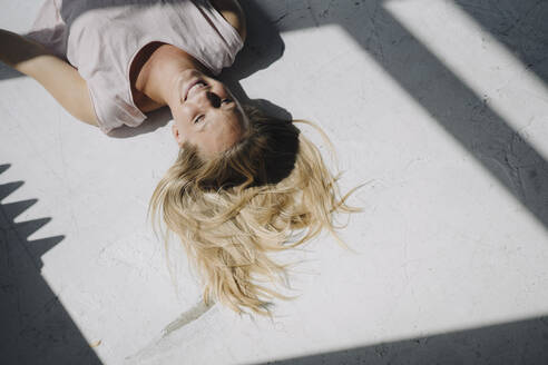 Smiling blond young woman lying on the floor in sunlight - KNSF07393
