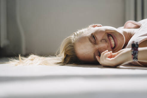 Portrait of happy blond young woman lying on the floor with closed eyes - KNSF07396