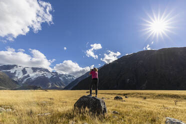 New Zealand, Oceania, South Island, Canterbury, Ben Ohau, Southern Alps (New Zealand Alps), Mount Cook National Park, Aoraki / Mount Cook, Woman standing on boulder and photographingmountain landscape - FOF11662