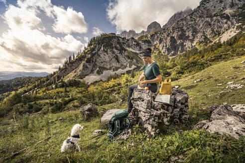 Woman with dog on a hiking trip at Wilder Kaiser having a break, Kaiser mountains, Tyrol, Austria - MSUF00171