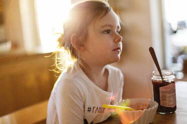 Girl at table looking away - JOHF06248