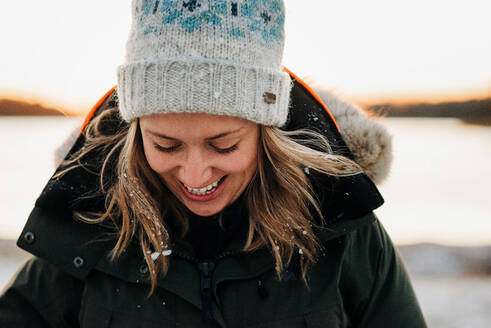 Portrait of woman with snow in her hair laughing at sunset - CAVF73738