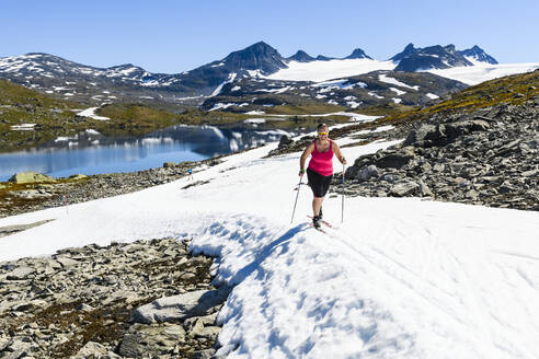 Woman cross-country skiing in mountains - JOHF06715
