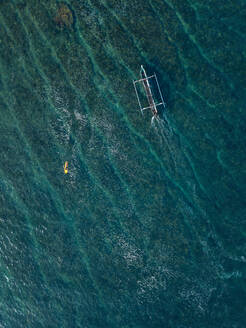 Aerial view of surfer and boat in the ocean - CAVF74104
