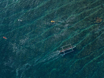 Aerial view of surfers and boat in the ocean - CAVF74107
