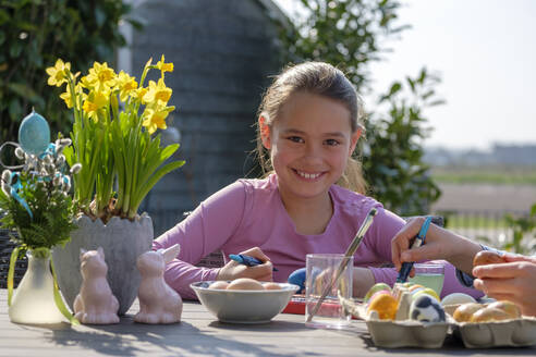 Portrait of happy girl sitting at garden table painting Easter eggs - LBF02859