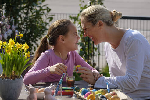 Happy mother and daughter painting Easter eggs at garden table having fun - LBF02862