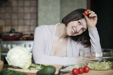 Portrait of happy woman preparing salad in kitchen - EYAF00913