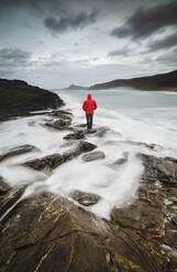 Back view of man standing in a coastal landscape, Ferrol, Spain - RAEF02318