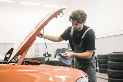Car mechanic in a workshop working at car checking dipstick - MOEF02753