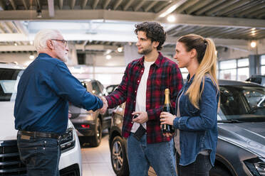 Couple buying new car at car dealership - MOEF02789