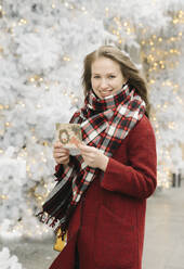 Portrait of smiling young woman standing on the street with Christmas card in front of white Christmas trees - AHSF01843