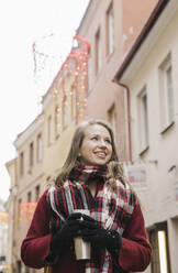 Portrait of smiling young woman with travel mug at Christmas time in the city - AHSF01846