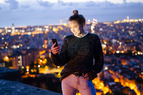 Young woman sitting on railing above the city using cell phone, Barcelona, Spain - GIOF07943