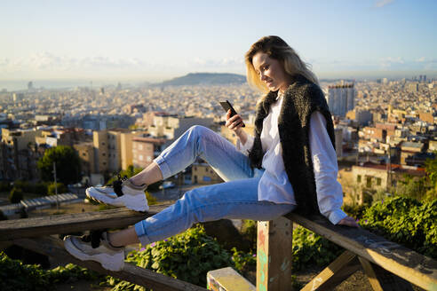 Young woman sitting on railing above the city using cell phone, Barcelona, Spain - GIOF07949