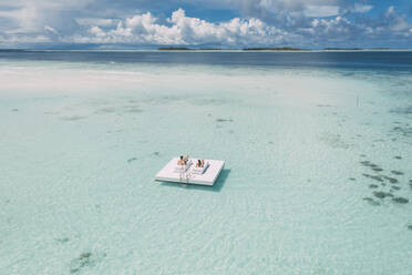 Couple lying on a platform in the sea, Maguhdhuvaa Island, Gaafu Dhaalu Atoll, Maldives - DAWF01216
