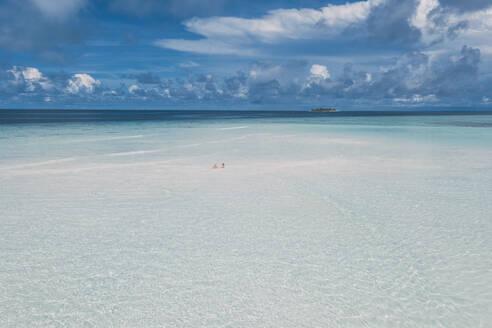 Woman lying on a sandbank in the sea, Maguhdhuvaa Island, Gaafu Dhaalu Atoll, Maldives - DAWF01219